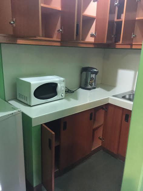 小さなキッチンには電子レンジ、ポット、冷蔵庫があります。